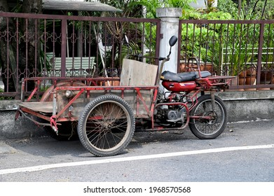 "Bangkok,Thailand - May 4, 2021 : Freight tricycles parking in slum community in Thailand.Red Car for business purchase antiques and Thai people call ""Saleng"""