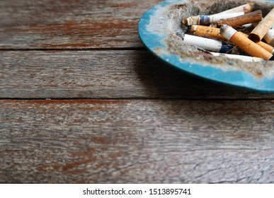 Bangkok/Thailand : May 7.2019 : Cigarette butts in an old cigarette tray on old wood table in a cafe with copy space- concept of heavy smoking / quit smoking / night life and health effect