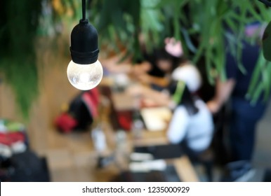 Bangkok/Thailand - November 17,2018 : Closeup of a light bulb with a blurred background of  young people working together in a co-working space cafe.