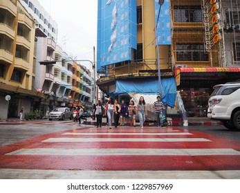 Bangkok-Thailand. November 6, 2018: Man and woman crossing road on the traffic way.