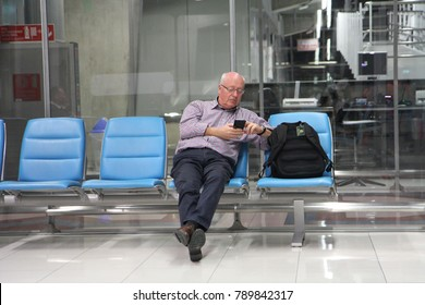 Bangkok/Thailand - October 13 2016 : a man sitting on passenger seats in airport, using smartphone