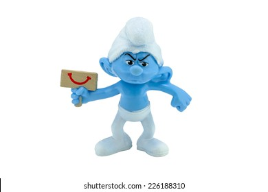 Bangkok,Thailand - October 2, 2014: Grouchy Smurf hold a happy sign toy figure model character from The Smurf movie.  There are plastic toy sold as part of the McDonald's Happy meals.