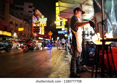 Bangkok,Thailand - Sep 12 - 2018: Chef cooking stir fried in a frying pan on Yaowarat road at night,the main street of Chinatown in Bangkok.Chinatown is famous landmark in Bangkok.