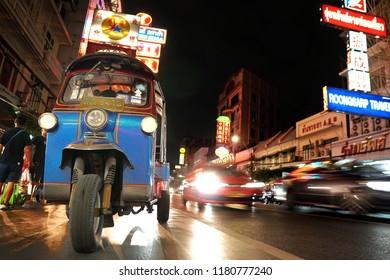 Bangkok,Thailand - Sep 12 - 2018: Tuk-Tuk on Yaowarat road at night,the main street of Chinatown in Bangkok.Tuk-Tuk is the name of Thai traditional taxi.Chinatown is famous landmark in Bangkok.