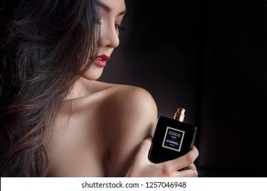 Bangkok,Thailand Sep 27, 2016: Sexy Sensual Beautiful Woman Applying Coco Chanel Noir Black Perfume. Paris. France. Luxury Black Bottle fragrance perfume Young Sexy Girl  Red Lips on dark background.
