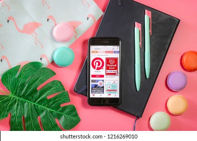 BANGKOK,THAILAND -September 23,2018: Flat lay photo Apple iPhone7 with Pinterest application on the screen notebook , Pencil , Macaroon,Flamingo bag , Tropical leaves and Smartphone on Pink background