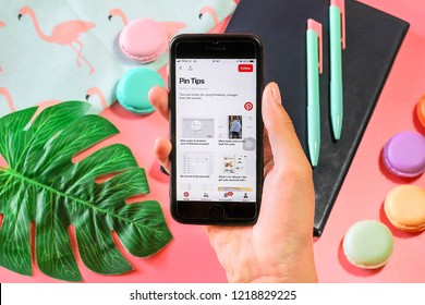 BANGKOK,THAILAND -September 23,2018: Hand holding Apple iPhone 7  with Pinterest application on the screen notebook , Pencil , Macaroon,Flamingo bag and Tropical leaves  on Pink background
