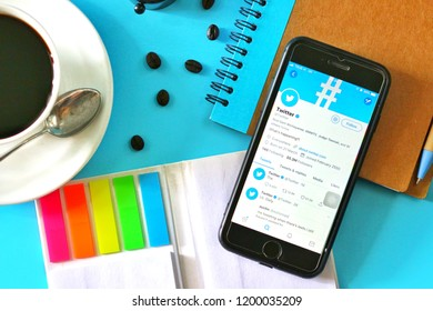 BANGKOK,THAILAND - September 23,2018:Flat lay photo with Apple iPhone7 opened Twitter app on the screen with Coffee cup ,Notebook ,Pen and coffee beans on Blue background