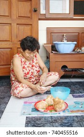 BANGKOK,THAILAND – SEPTEMBER 3, 2017: Old women happy cooking (scratch coconut) sitting in the terrace, prepare making coconut milk. Coconut on the red tray. Scratched cocunut in the blue plastic bowl
