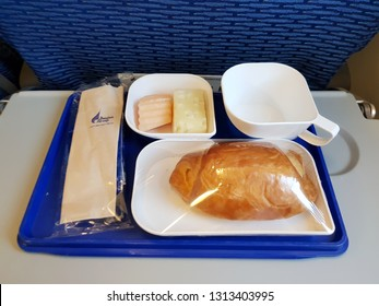 Bangkok,Thailand-5 February 2019: Bangkok Airways dishes out an in flight meal for a short domestic route in an economy class with fruits and a simple chicken sausage croissant wrapped in plastic.