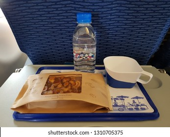 Bangkok,Thailand-8 February 2019: Bangkok Airways dishes out an in flight meal for a short haul economy class with a toffee cake wrapped in a paper package and a bottle of water putting on blue tray.