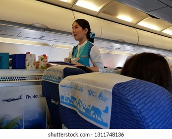 Bangkok,Thailand-8 February 2019: Flight attendant of Bangkok Airways carries the food and drink trolley cart for serving the in flight meal to passengers in economy class.