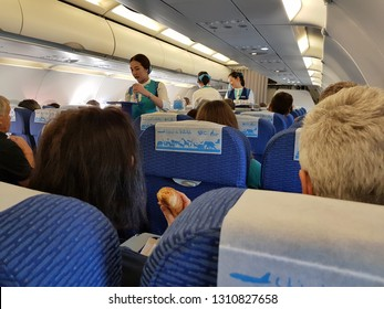 Bangkok,Thailand-8 February 2019: Flight attendants of Bangkok Airways work on their duty holding beverages tray to serving to passengers in economy class.