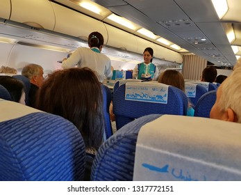 Bangkok,Thailand-8 February 2019: Flight attendants of Bangkok Airways carries the food and drink trolley cart for serving in flight meal to passengers in a short haul economy class.