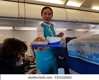 Bangkok,Thailand-8 February 2019: Friendly professional flight attendant of Bangkok Airways holds a food tray of in flight meal on one hand and smilingly brings it to the economy class passenger.