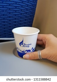Bangkok,Thailand-8 February 2019: A hand holds a paper cup presented with brand logo of Bangkok Airways putting on passenger table placing into a small round holder space.