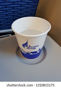 Bangkok,Thailand-8 February 2019: A paper cup presents with brand logo of Bangkok Airways putting on passenger table placing into a small round holder space. It contains mineral water.