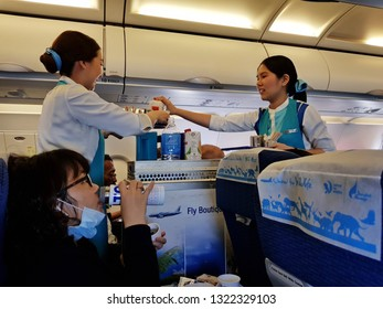 Bangkok,Thailand-8 February 2019: Two female flight attendants of Bangkok Airways help each other to carry food and drink trolley to providing the in flight meal service to passengers.