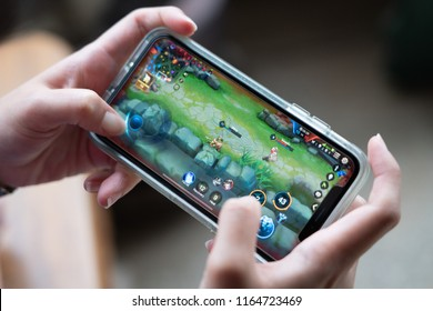 BANGKOK,THAILAND-AUGUST 26: View of female hands playing Realm of valor ROV  a Moba game application display on mobile screen on August 26,2018