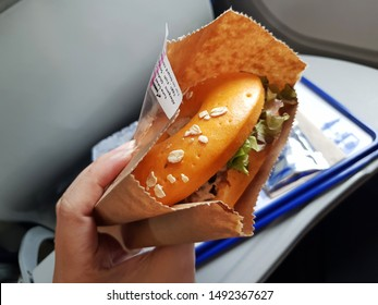 Bangkok,Thailand-Circa August 2019: Bangkok Airways dishes out the in flight meal serving sandwich in papar bag at day for passenger and a hand holding it.