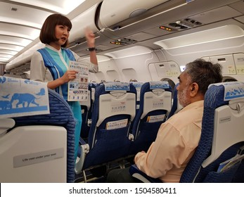Bangkok,Thailand-Circa August 2019: Cabin crew of Bangkok Airways stands showing the safety instruction card in hand to passenger who sits at the emergency exit doorway.