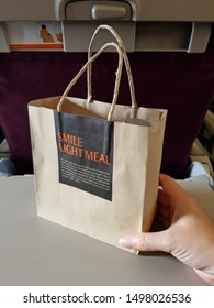 Bangkok,Thailand-Circa August 2019: A hand of passenger holds a paper bag of light meal provided by Thai Smile airways on plane table in economy class at day flight.