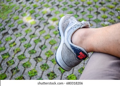 BANGKOK,THAILAND-CIRCA JUL 2017:The man wearing Nike shoes accessories for fashion during a sit-in with a brick and grass floor is the background of this picture.