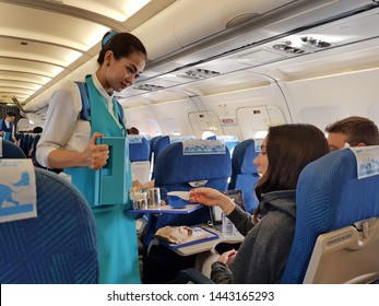 Bangkok,Thailand-Circa June 2019: Friendly professional flight attendant of Bangkok Airways wears blue uniform and smilingly serves coffee as in flight beverage to the economy class passengers at day.