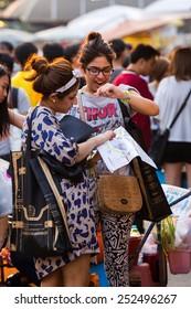 BANGKOK,THAILAND-FEBRUARY 9 2015: Tourists search a map at Jatujak Market or JJ Market a famous and celebrated tourist attraction with souvenirs, appliances, artwork, garments and food.