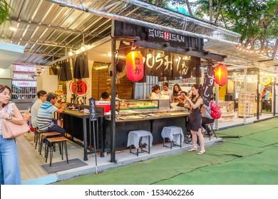 BANGKOK,THAILAND-March 2019-People eating Japanese food at Sushi restaurant. Outdoor street food night market. Market Stalls. Outdoor market. Food Event. Food Fair. Festival. Flea Market. Bazaar