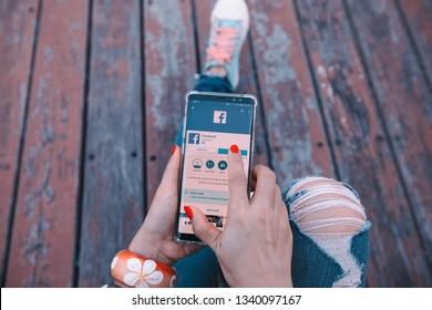 BANGKOK-THAILAND-MARCH-7-2019:Woman hand using Samsung note5 Facebook social media app logo install application,menu on smartphone screen,Facebook is a popular social media application for sharing