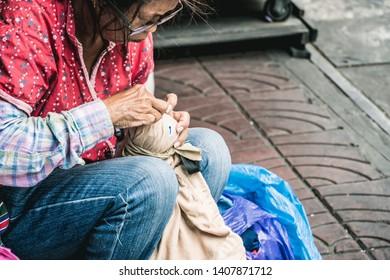 BANGKOK,THAILAND-MAY26,2019:Old elderly woman sewing a quilt by hand at Chinatown Bangkok.