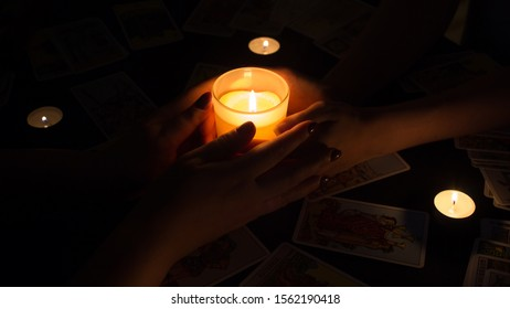 Bangkok,Thailand,november.17.19. Night divination with candles. Seance and prediction of the future. Female hands hold a lighted candle in the dark at night. A fortune teller performs a magical ritual