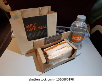 Bangkok,Thailand-September 2019: Thai Smile airline provides paper bag of light meal packed with sandwich and water for economy class passengers in flight. Food and drink packages put on plane table.