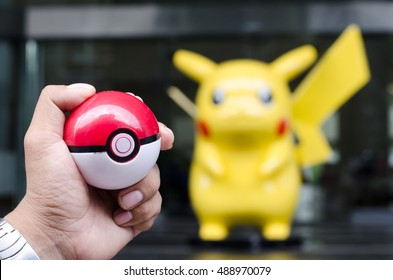 BANGKOK,THAILAND-September 29, 2016 : Hand holding a Pokeball in front of a giant Pikachu mascot at Nisson Showroom. Concept of Pokemon trainer trying to catch Pokemon.