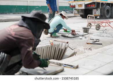 BANGKOK,THAILAND-SEPTEMBER19,2019:Engineer cut concrete with concrete saw or Electric grinder tool,fix sidewalks that are chipped and pitted at Sukhumwit,Bangkok