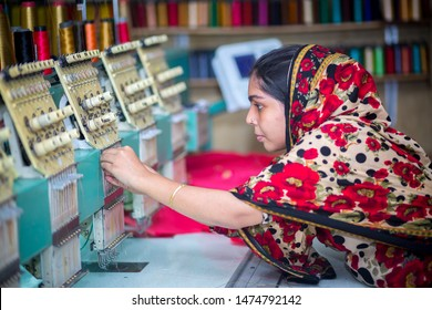 Bangladesh – August 6, 2019: A Bangladeshi woman garments worker working with Computerized Embroidery Machine at Madhabdi, Narsingdi, Bangladesh.