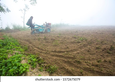Bangladesh – January 06, 2014: On a foggy winter morning, a farmer is plowing his land with a 2-wheel tractor at Ranisankail, Thakurgaon.