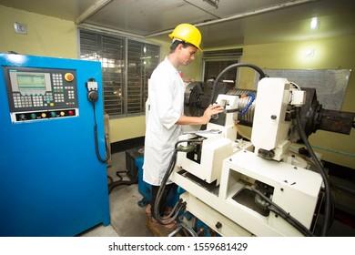 Bangladesh – May 20, 2015: A factory lab operator using Steel rod quality testing machine at Demra, Dhaka, Bangladesh.