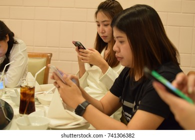 Bangna Thailand, Oct 20, 2017, Social Ignore, Social Phubbing, A group of young girl asian playing with mobilephone while talking a break in dining room