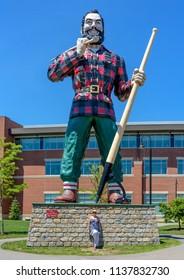 BANGOR, MAINE - July 4, 2018: Huge Paul Bunyan Statue in Downtown Bangor Maine with a Female Tourist