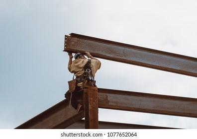 Bangor, Maine / USA - 4-21-2018: US Steel Worker Guiding Metal Beam on CIANBRO Work Site