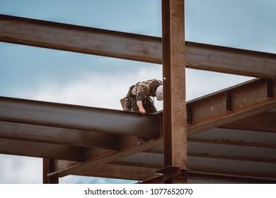 Bangor, Maine / USA - 4-21-2018: US Steel Worker Lining Up Beam on CIANBRO Work Site