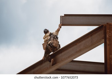 Bangor, Maine / USA - 4-21-2018: US Steel Worker Reaching for Metal Beam on CIANBRO Work Site