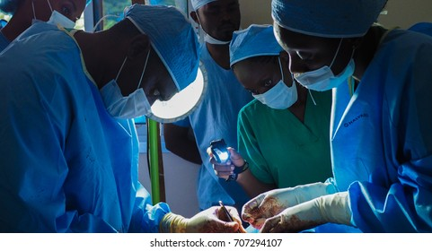 Bangou, Cameroon - July 9, 2016: Surgeons operate on a patient at a mobile hospital in Cameroon while medical students observe.