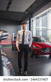 BANGSEAN MAY 2019:Man asian business saleman with red car in mazda showroom sale car.For automotive automobile or transport transportation Illustrative editorial image.