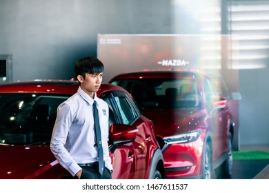BANGSEAN MAY 2019:Man asian business saleman with red car in showroom sale car.For automotive automobile or transport transportation Illustrative editorial image.