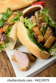 Banh mi - Vietnamese tea smoked duck sandwich with salad and dipping sauce.