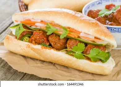 Banh Mi Xiu Mai - Vietnamese sandwich with meatballs in tomato sauce, do chua (radish and carrot pickle), cucumber and coriander.