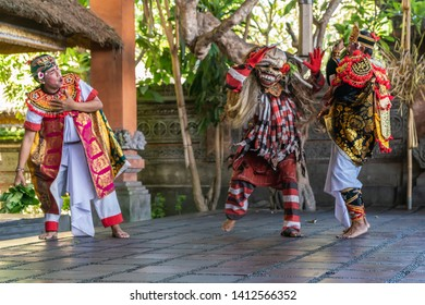 Banjar Gelulung, Bali, Indonesia - February 26, 2019: Mas Village. Play on stage setting. Fleeing Orator in white attacked by man in ugly mask and colorful garments. Other guy tries to stop fight.